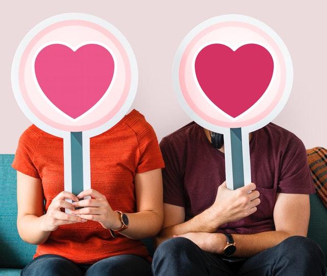 Muž a žena si pred tvárou držia ceduľky s veľkými ružovými srdcami.jpg