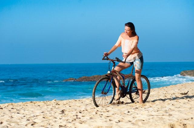 Žena v ružovom tričku ide na bicykli po pláži.jpg