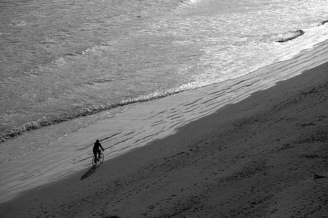 Osoba ide na bicykli po pláži počas prílivu.jpg