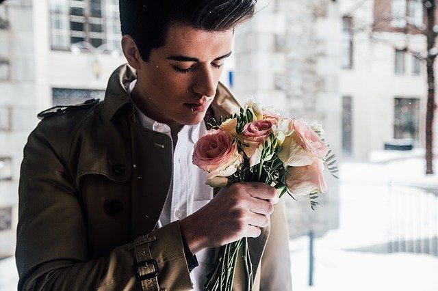 Mladý muž v hnedom kabáte drží v rukách kyticu kvetov.jpg